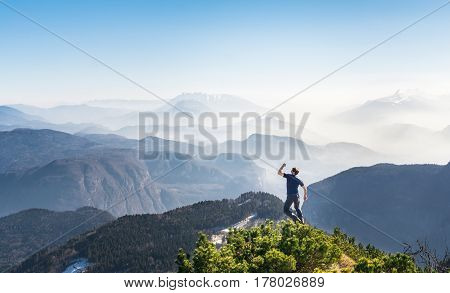 Happy celebrating winning successful man jumping with arm raised up above his head and clenched fist in celebration of having reached mountain top summit goal achieve during hiking travel trek in the Alps.
