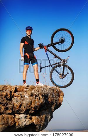 Man biker holding bike on the top of a hill against beautiful blue sky. Extremal sport concept. Beautiful landscape. Power and energy. Sportsman in the blacksportwear, helmet and sunglasses. Travel in the countryside. Spring season.
