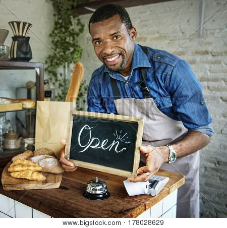 African Man Holding Open Sign in Bakery Shop