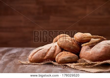 handmade tasty bread lying on burlap on the wooden table with flour, wheat and ears of wheat. Brown blurred background. Brown bread and rulls. Delicious food. Fresh baking. Tasty and appetizing.