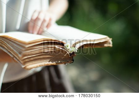 A young girl is holding a very old shabby book in her hands. Summer sunny day horizontal shot.
