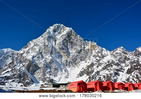 Row of the red tents way from Cho-La pass to the Everest base camp Nepal. Magnificent Himalayan mountains on the background.