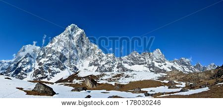 Majestic Himalayan mountains Nepal. Panoramic view of the mountain ridge covered with snow on the background of deep blue sky.