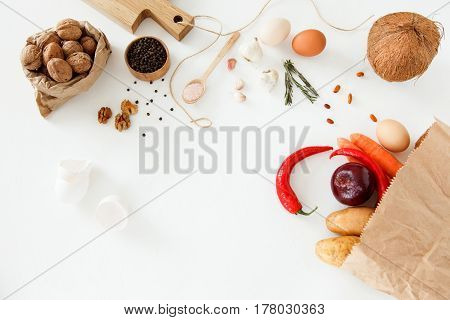 Vegetables nuts beans potatoes red peppers chicken eggs other food and kitchen appliances lie on a white background. Space for text daylight horizontal image.