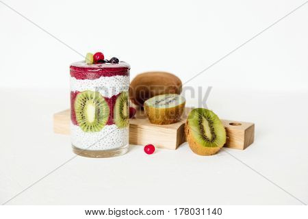 Smoothies in a glass on a white background with berries and fruits blueberries kiwi and chia seeds. Horizontal image daylight space for text.