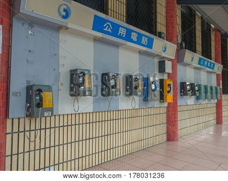 Luodong Taiwan - October 18 2016: More than a dozen of phones installed on the wall of a railway station building in Luodong