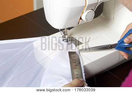 A Woman Works On A Sewing Machine. She Sews The Curtains On The Window. Using The Ruler, It Makes Me