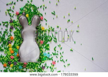 Easter background with cookie cutter and sugar sprinkles
