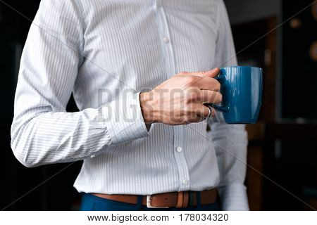Close up of a businessmans hand with a cup of coffee. A beautiful white shirt and blue pants.