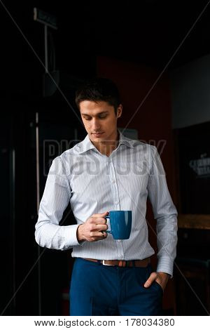 Businessman having coffee break, he is holding a cup. Young man dressed formal.