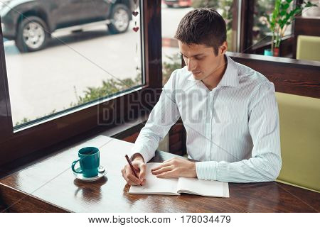 Businessman having a cup of coffee in office. Young man writing in notebook on brown wooden table with cup of coffee.