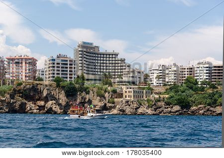 High contemporary house on a rocky beach in the background yachts and ships Antalya, Turkey - July 29, 2015: View of the city of Antalya from the sea