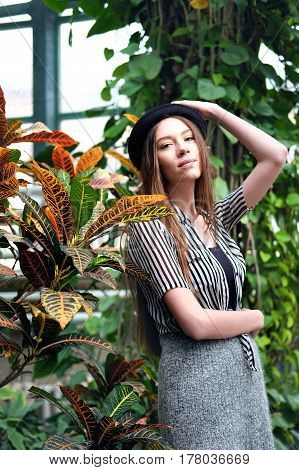 Beautiful long chestnut hair in black hat posing in among tropical plants in greenhouse.