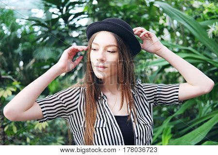 Beautiful long chestnut hair caucasian woman in black hat posing in among tropical plants in greenhouse.