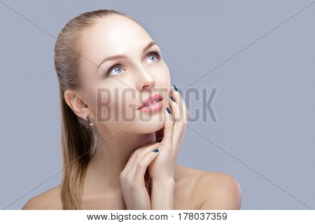 portrait of beautiful young blonde woman with blue eyes on grey background closeup.  Woman Touching her Face