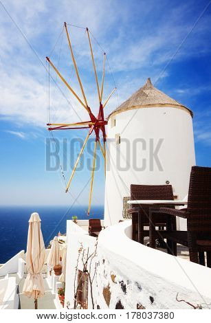 windmill of Oia at sunny day with blue sea and sky close up, Santorini, toned