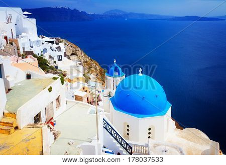 view of caldera with blue church dome and belltower, Oia, Santorini, retro toned