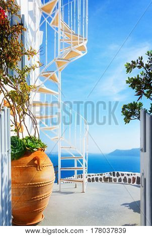 beautiful details of Santorini island - house staircase with flower in pot and blue sea, Greece, retro toned