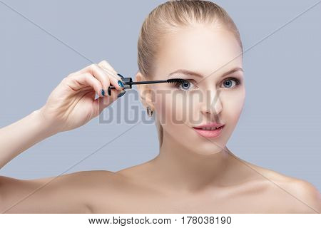 beautiful blond woman applying makeup on face on gray background. perfect makeup for blue eyes. the brush of mascara
