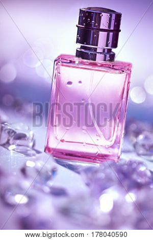 Perfume in glass transparent bottle with water droplets and pieces of ice around. Photo of bottle perfume on blurred pink background. Beauty concept