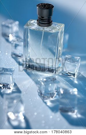 Men's Perfume in transparent bottle with water droplets and pieces of ice around on blue background. Studio photography of perfume bottle. Male beauty concept