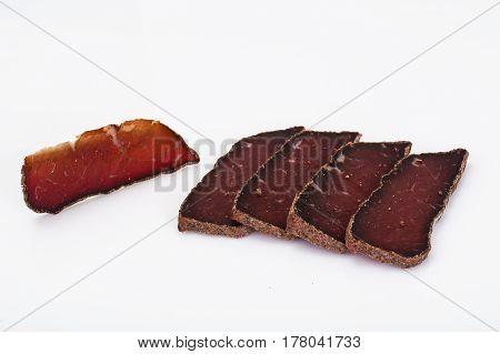 Dried beef basturma, chopped on white. Studio Photo