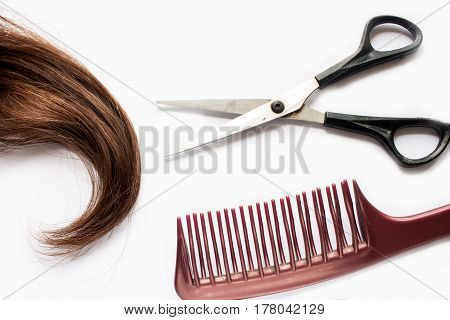 A Pair Of Scissors, Dark Brown Hair And Comb On White Background