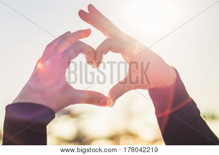 Heart from hands in the background of the sun