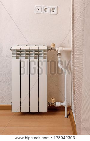Modern hot water radiator on the wall side view