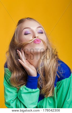 portrait of beautiful blond woman in casual colorful vivid summer clothes making a mustache with her long hair on yellow background