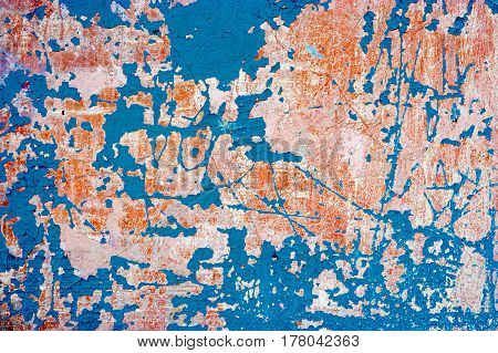 Abandoned wall with blue paint on. Grungy background with weathered plaster and destroied paint.