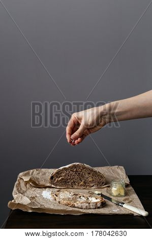 Woman Sprinkling Salt onto Slice of Wholegrain Bread on Table