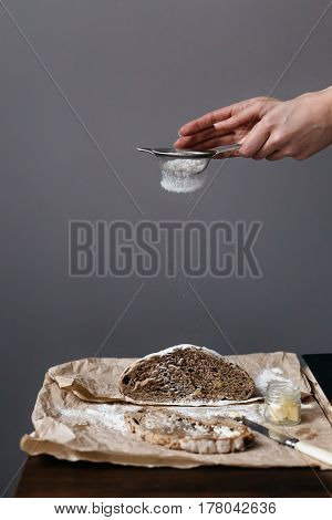 Woman Sieving Flour onto Loaf of Bread on Table