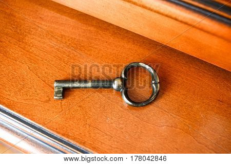 Old Retro Vintage Classic Key On Polished Wooden Cupboard. Key To Old Mystery