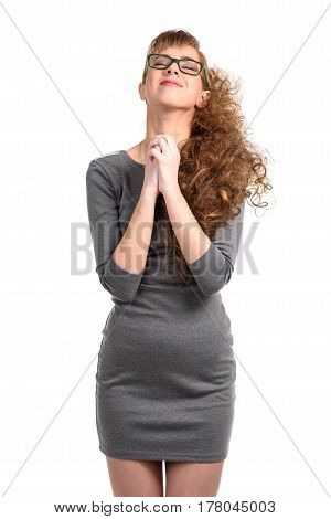 Cheerful woman with praying hands and eyes closed isolated on white.