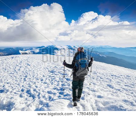 Dreaming girl is sitting on snowy hill at the high mountains watching mountain scenery and nature in frosty winter day.
