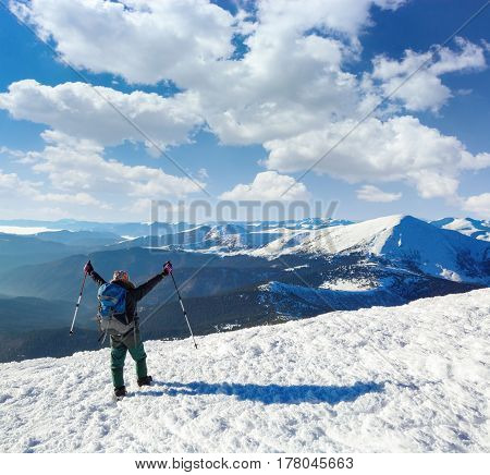 The tourist with big back sack and hiking sticks is going to the goal through the snowy lawn and before the view there are unbelievable beautiful mountains covered with snow and blue sky