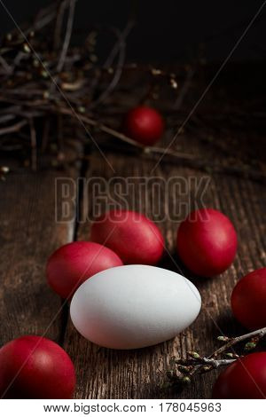 Easter eggs of red color and one white egg on a wooden background together with autumn branches