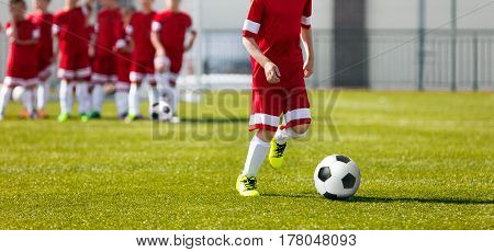 Soccer Football Training for Kids. Youth Soccer Academy Training. Boy Kicking Soccer Ball