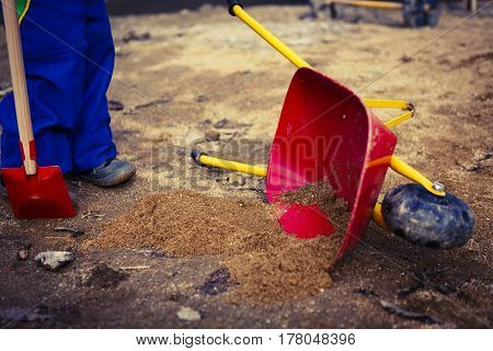 Child Play With Sand, Red Shovel And Small Cute Barrow