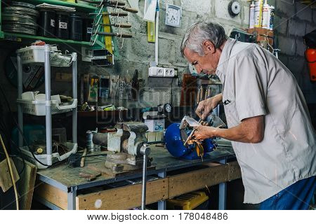 Unrecognizable professional worker grinding metal with flash of sparkles