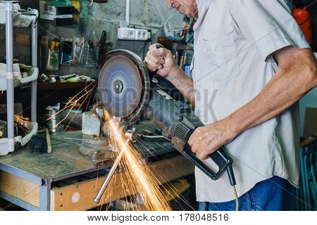 Side view of senior workman working with circular grinder in his hands producing flash of sparkles