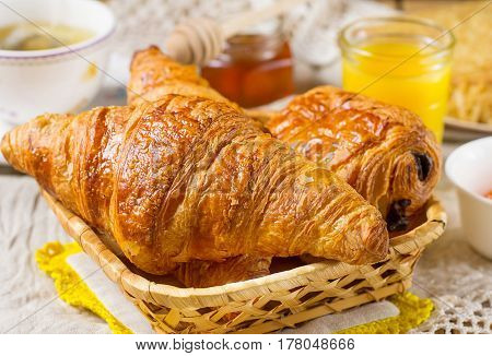 Croissants viennoiserie pastry for breakfast with tea and orange juice