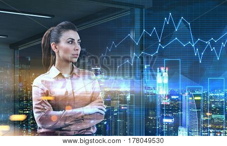 Portrait of a woman trader wearing a brown blouse and standing with crossed hands in her office at nigth. There are graphs in the air. Toned image. Double exposure.