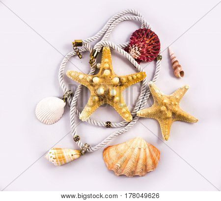 Sea Themed Composition: Shells, Starfish And Pearls On Blue Material Fabric Background