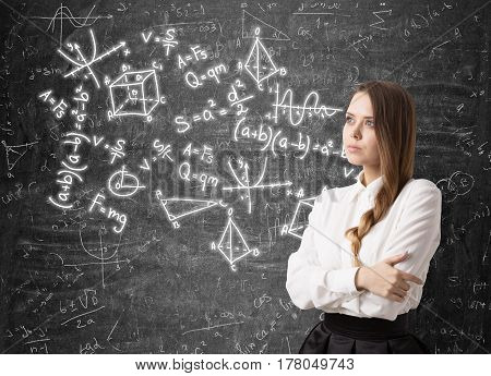 Portrait of a serious woman with braided hair standing with crossed arms near a blackboard with math formulas written on it.