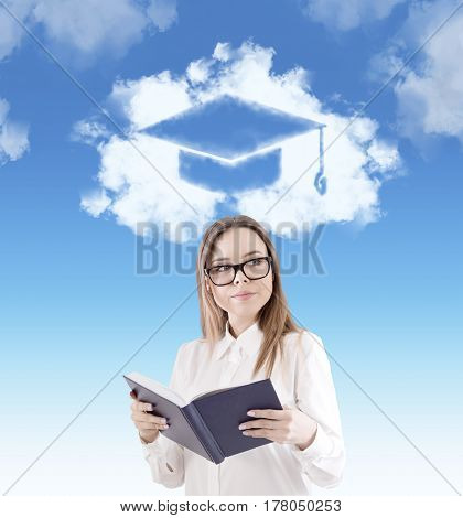 Portrait of a nerd girl wearing glasses and holding a book. There is a graduation hat sketch in the sky above her head.