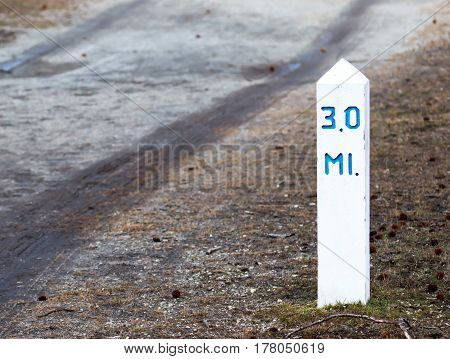 The 3 mile marker for runners bikers and walkers on a running path in a state park.