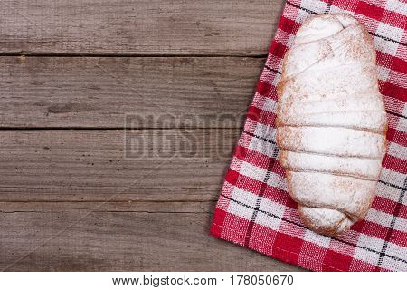 one croissant sprinkled with powdered sugar on old wooden background with copy space for your text. Top view.