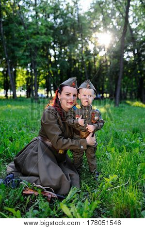 A small son with his mother in the uniform of a Soviet soldier against the background of nature. May 9, Victory Day, World War II, family, peace, against fascism.